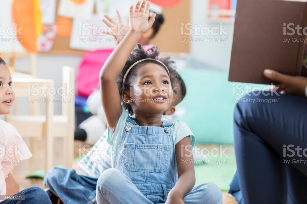 Little girl raises her hand during story time stock photo
