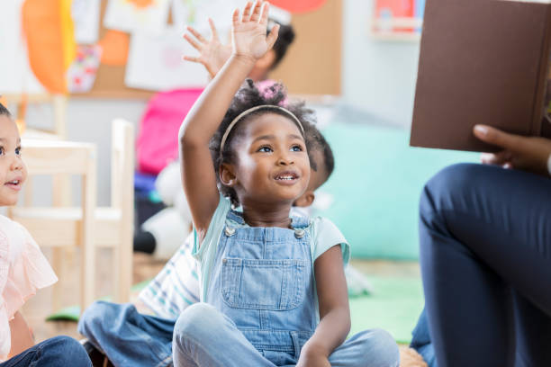 niña levanta la mano durante el tiempo de la historia - clase de idiomas fotografías e imágenes de stock