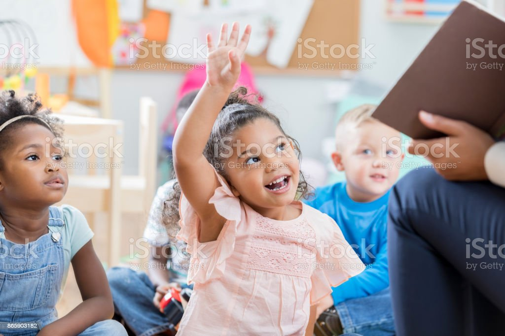 Little girl raises her hand in class - foto stock