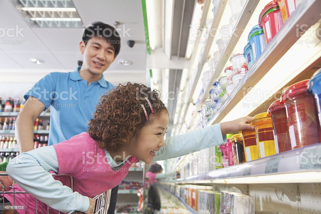 Little Girl Reaching for Food in Supermarket stock photo
