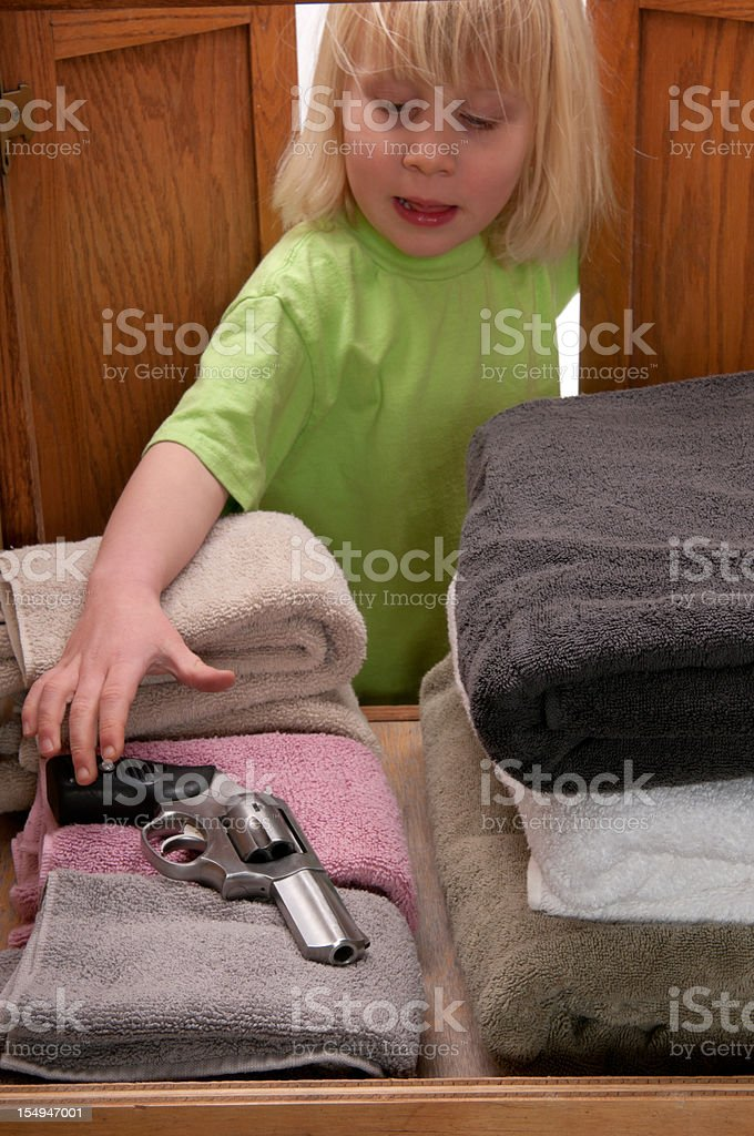 CHILD SAFETY SERIES-#4 little girl reaching for gun stock photo
