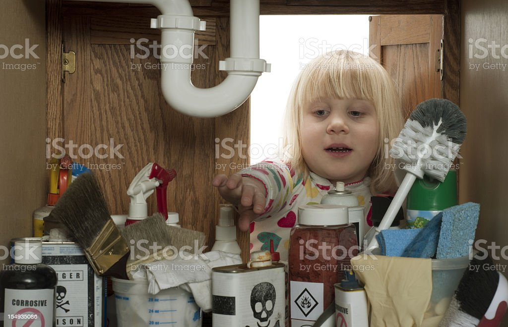 CHILD SAFETY SERIES-#2 little girl reaching under sink stock photo