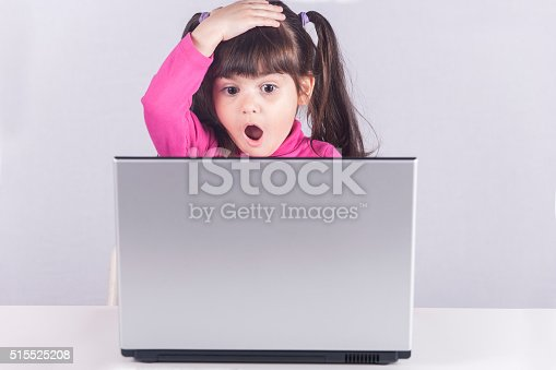 istock Little girl reacts while using a laptop 515525208