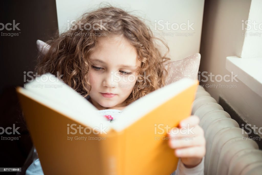 little girl read a book at the window stock photo