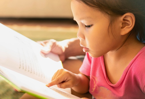 A young child pointing at words on a book, concentrating on learning how to read at home.