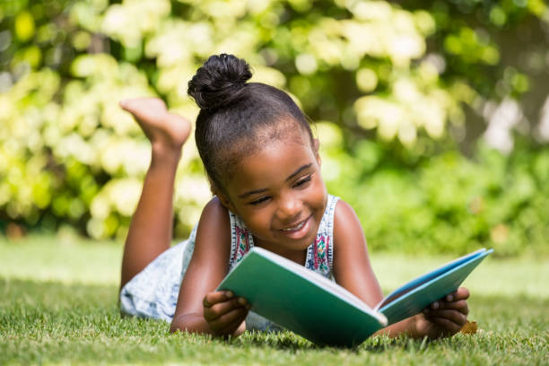 Little girl reading a book at park stock photo
