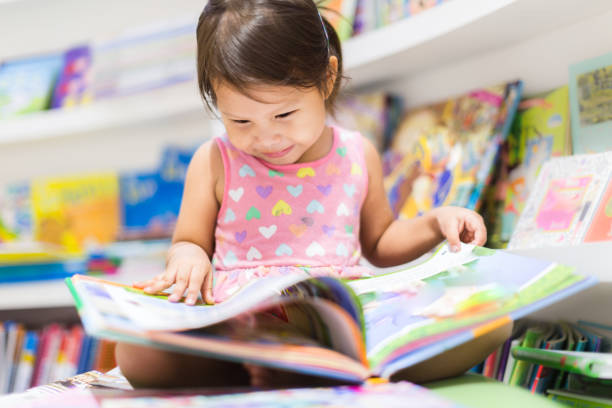 Little girl reading a book. Education. stock photo
