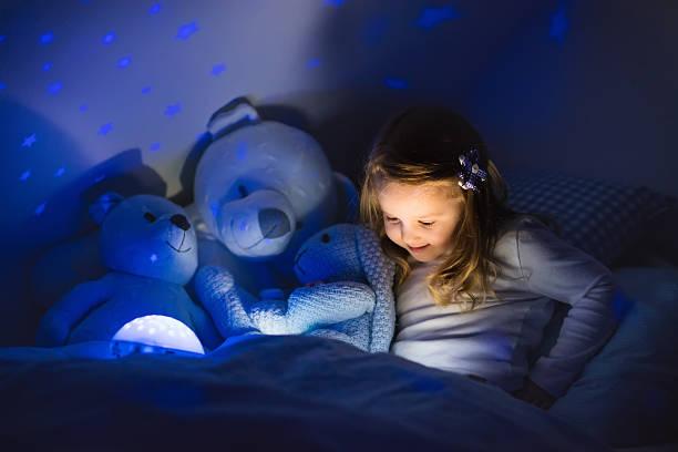kleines mädchen liest ein buch im bett - deckenleuchte kinderzimmer stock-fotos und bilder