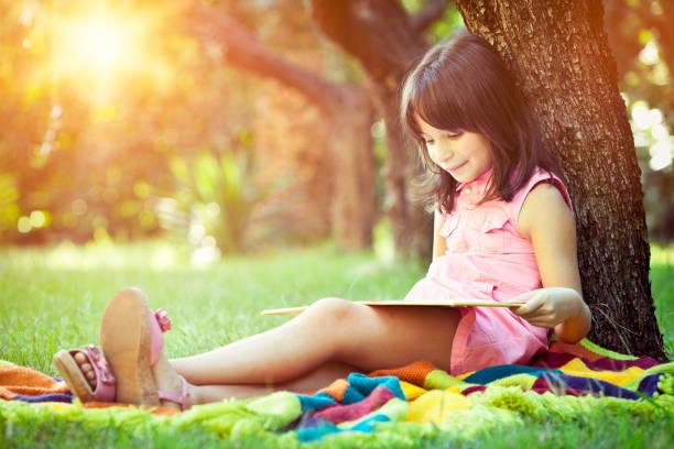 Kleines Mädchen liest ein Buch im park – Foto