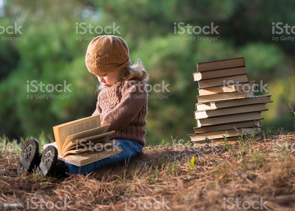 little girl reading a book in the park