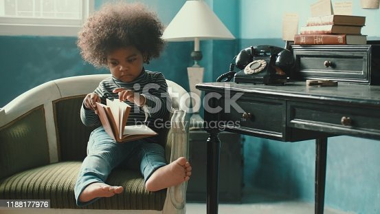 African-American little girl(2-3 years) reading book at home, Bangkok Thailand