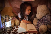 Little girl reading a book to her teddy bears