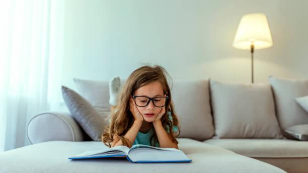Petite fille affichant un livre d'enfant à la maison - Photo