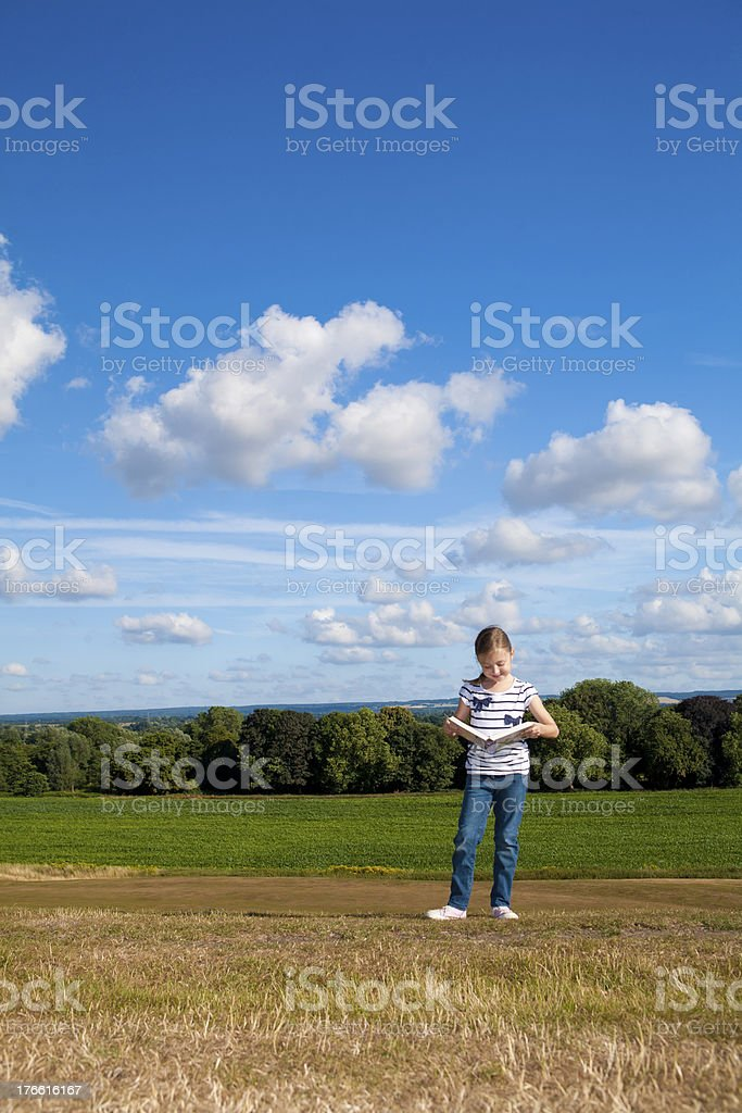 Little girl reading a story in the wide open space royalty-free stock photo