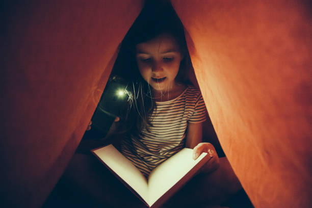 kleines mädchen einen terror-roman lesen - deckenleuchte kinderzimmer stock-fotos und bilder