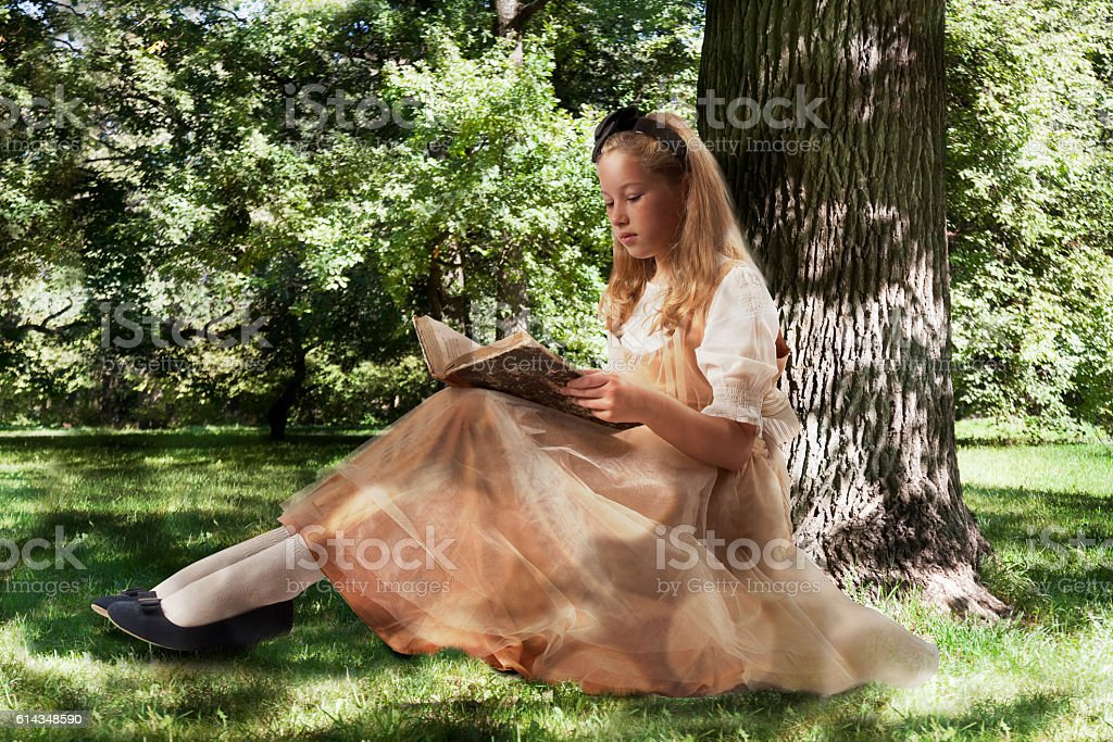 Little girl reading ancient book - foto de stock