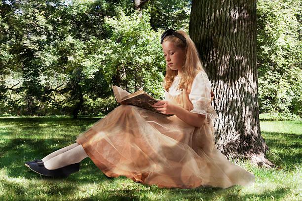 Little girl reading ancient book - foto de stock
