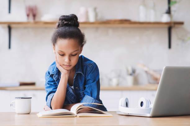 meisje lezen boek thuis - a little girl reading a book stockfoto's en -beelden