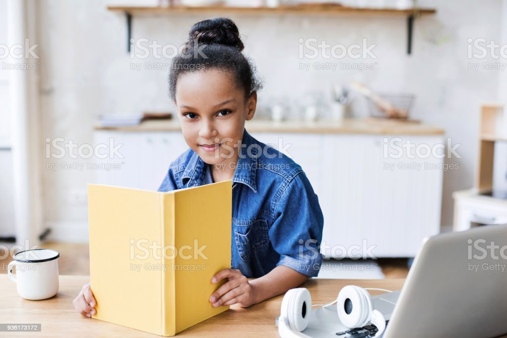 Little girl reading book at home stock photo