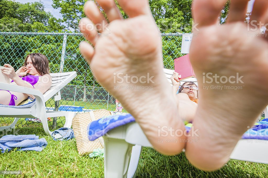 Little girl reading book in the chaise lounge stock photo