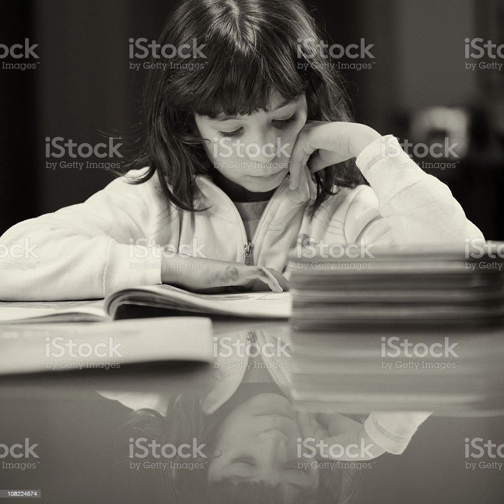 Little Girl Reading Book on Table royalty-free stock photo