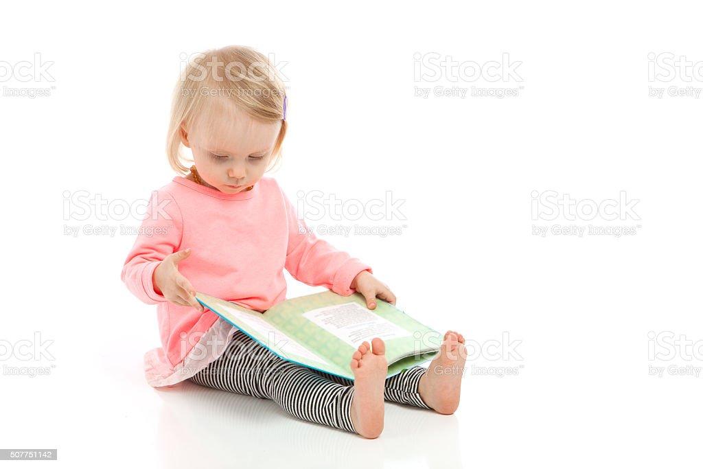 Kleines Mädchen liest ein Buch auf Weißer Hintergrund – Foto