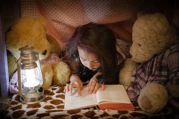 Little girl reading book to teddy bears in fort stock photo