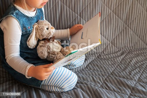 Little girl reading favorite book at home with her toy rabbit.