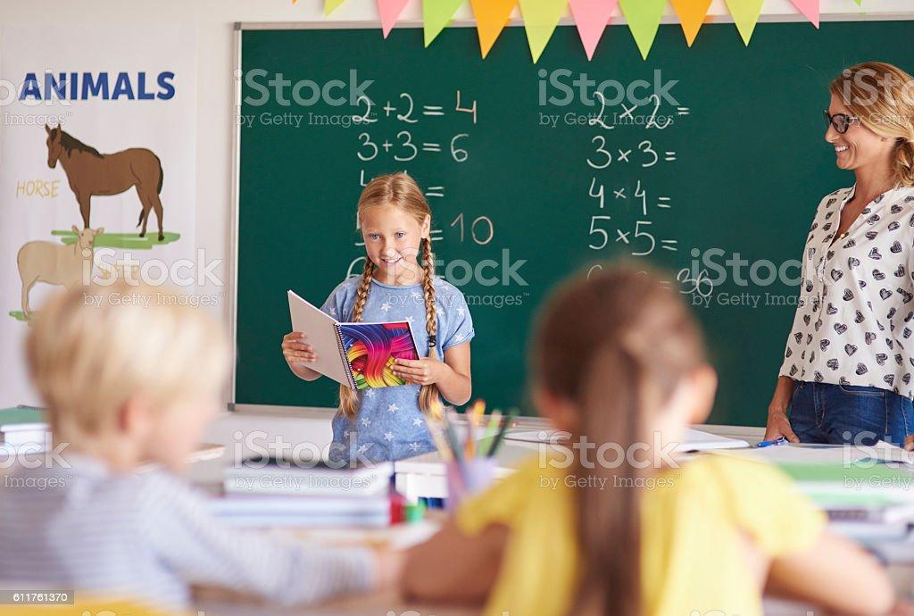 Little girl reading homework in the classroom stock photo
