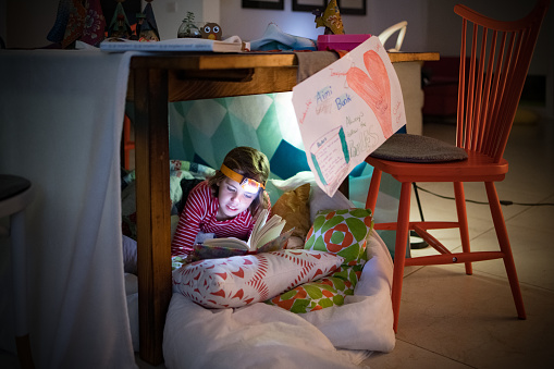 little girl reading in pillow fort stock photo download image now istock