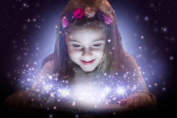 little girl reading magic book - fairy wand stock photos and pictures