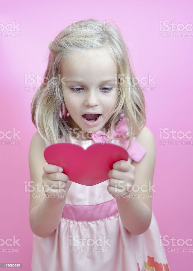 Little girl reading Valentine's card stock photo