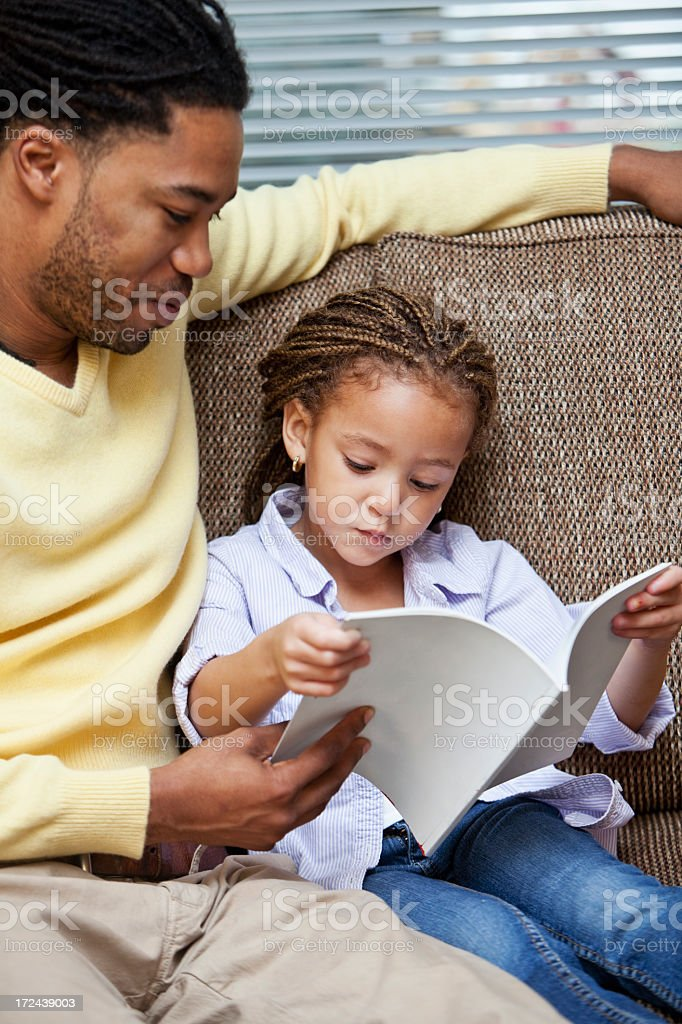 Little girl reading with father stock photo
