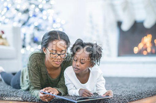 istock Little girl reading with her mom 1065950428
