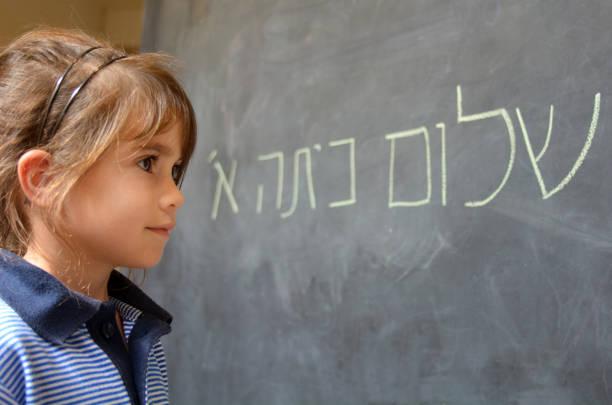little girl reads hello first grade greetings in hebrew - pismo hebrajskie zdjęcia i obrazy z banku zdjęć