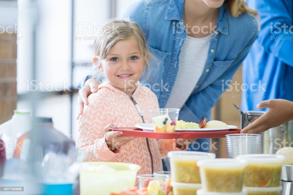 Adorable little girl holds a tray of healthy food in a soup kitchen.