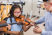 A smiling little girl sits next to her attentive music teacher and plays the violin during music class.  Her teacher adjusts the violin's position as she plays.