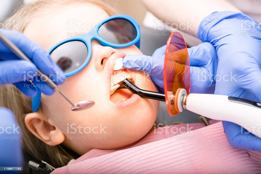 Dentist performing dental filling procedure to a little girl in...
