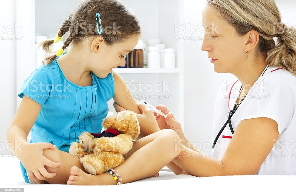 Little Girl Receiving Vaccine at the doctor's office stock photo