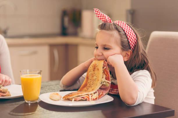 little girl refuses to eat breakfast - slow food foto e immagini stock