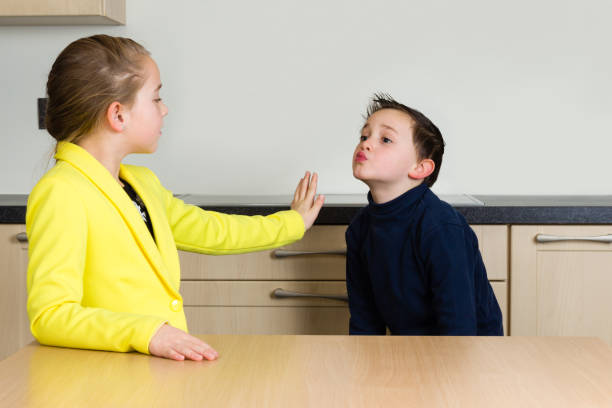little girl rejects little boy trying to kiss her - kids kiss embarrassed foto e immagini stock