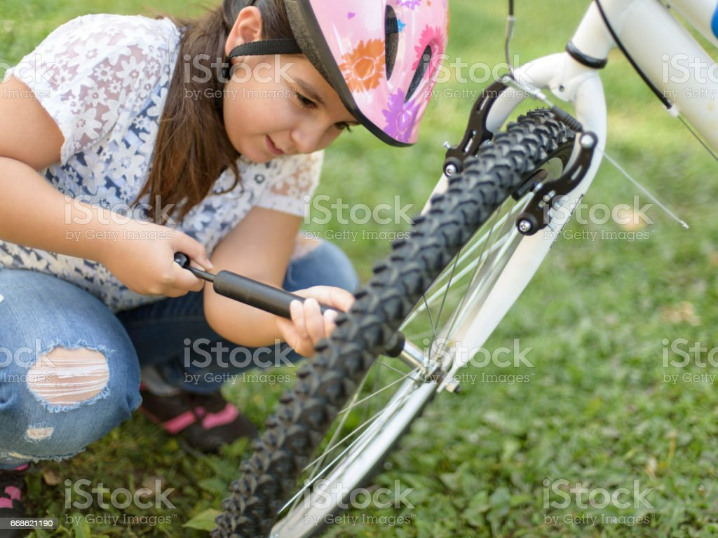 Little girl repairing a bicycle stock photo