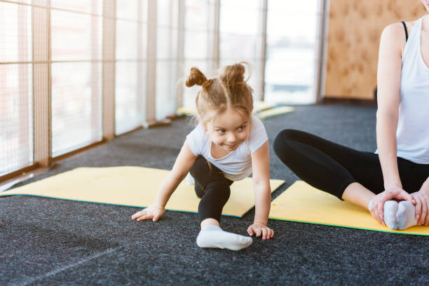 A little girl repeats exercises for her mother stock photo