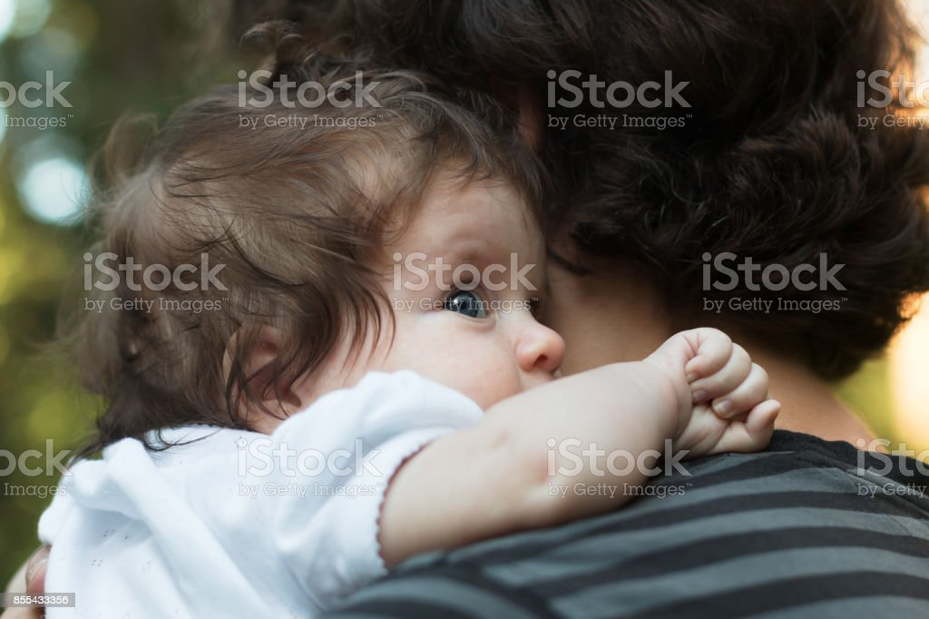 Little Girl resting on her father's shoulder. Happy sweet girl hugging her father on the forest background stock photo