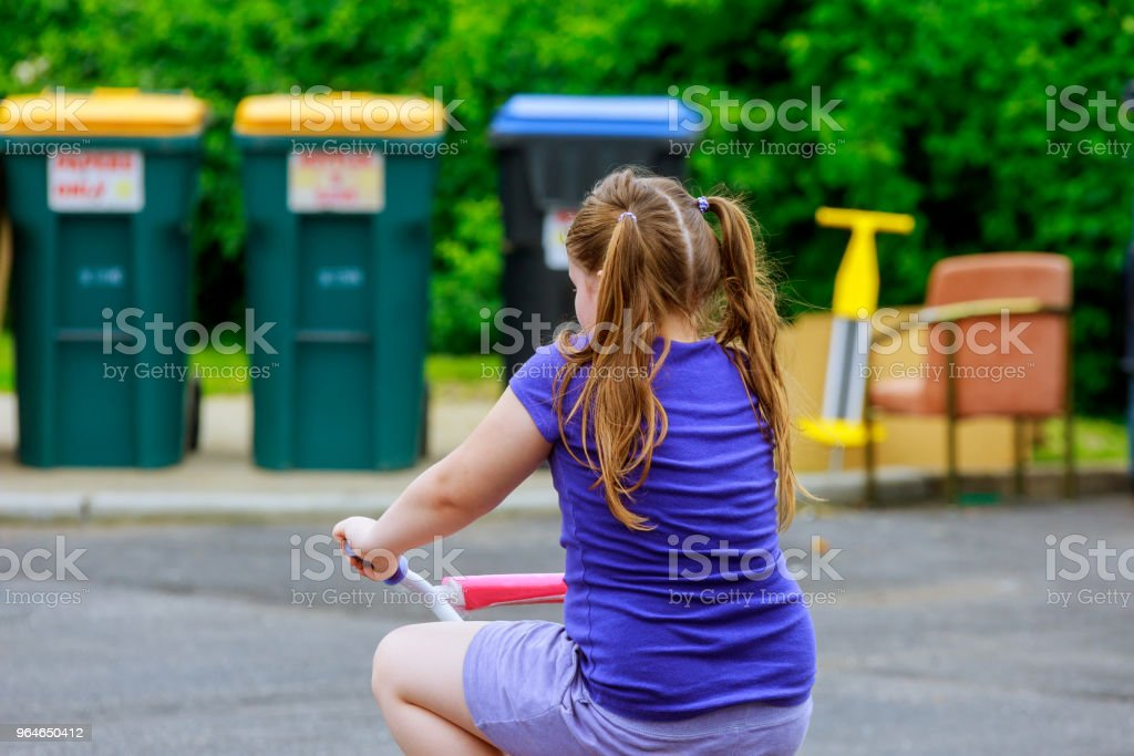 Little girl ride a pink bike from back in park royalty-free stock photo