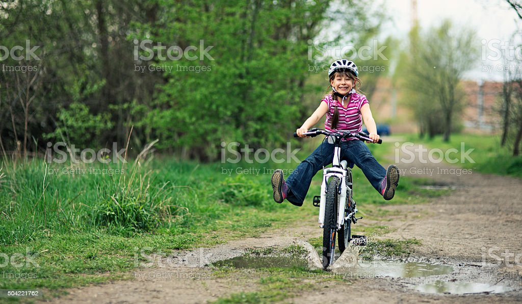 Little girl riding a bike  through a puddle. stock photo