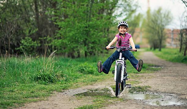 Little girl équitation un vélo dans une flaque. - Photo