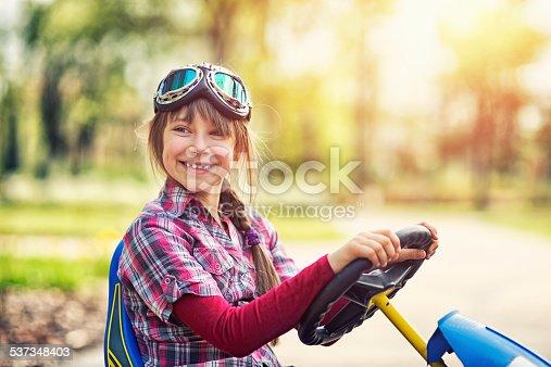 1035136022 istock photo Little girl riding a go-kart bike in park. 537348403