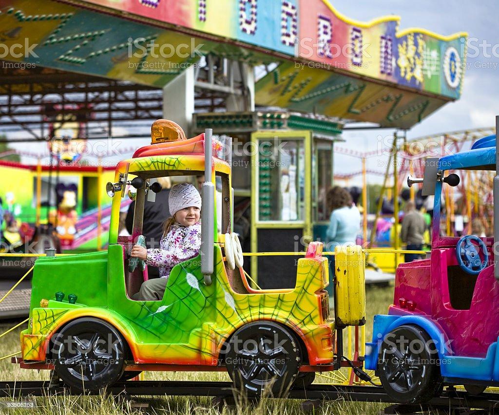 Little girl riding a kids train at an amusement park stock photo