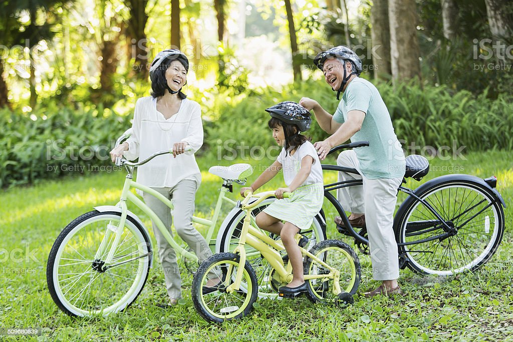 Little girl riding bicycles with grandparents stock photo